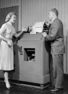 Old Photo of a man and women stading by old machine.